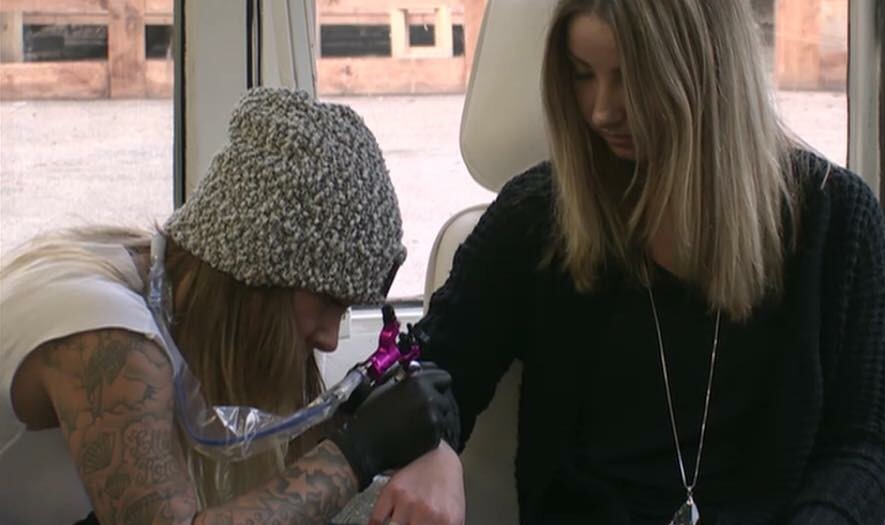 Laura zet een tatoeage