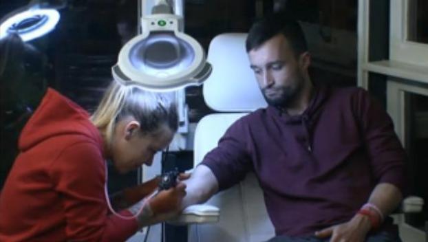 Laura zet een tattoo bij Mark