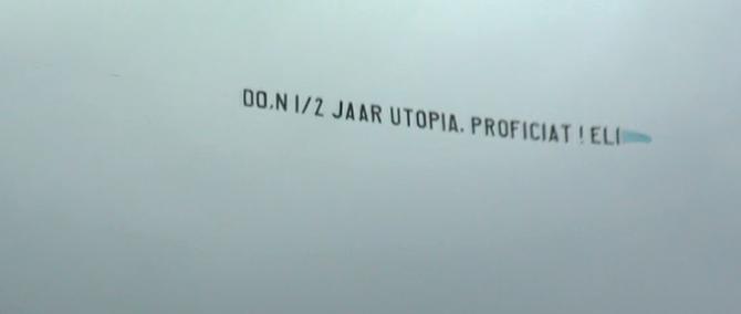 Een vliegtuigje over het Utopia terrein voor Do